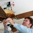 Electrician Removes Ceiling Fan - Stock Photo