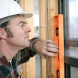 Stock Photo: Carpenter Leveling Window