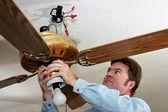 Elektrikçi tavan fanı kaldırır — Stok fotoğraf