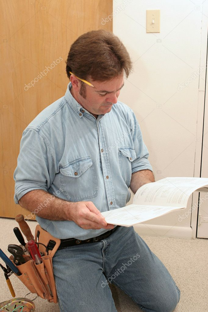 An electrician reading the manual to a ceiling fan prior to installing it. — Stock Photo #6671154
