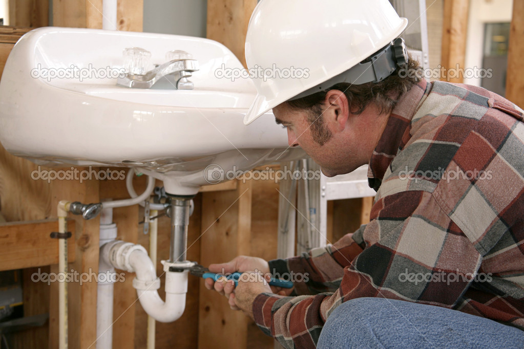A plumber in new home construction installing bathroom fixtures.  Focus on plumber's face.  — Stock fotografie #6671363