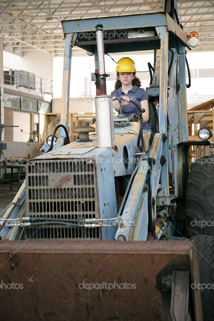 A female construction worker driving an earth mover on a construction site.  Stock Photo #6671426