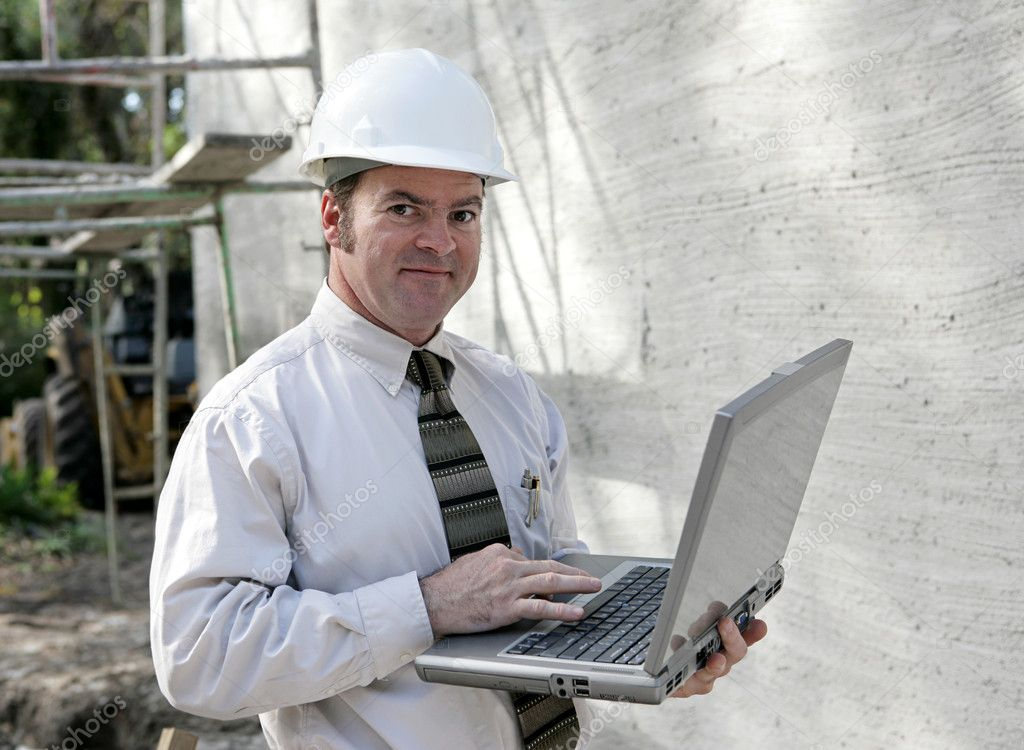 An engineer or building inspector checking building specs on his laptop computer.   — Stock Photo #6671509