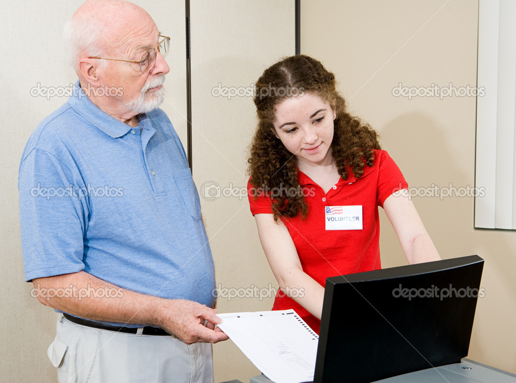 Teen volunteer helping senior voter use the new equipment on election day.   — Stock Photo #6673587