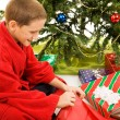 Boy Opens Christmas Present - Stock Photo