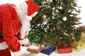 Santa Puts Gifts Under Tree — Stock Photo