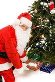 Santa under träd med presenter — Stockfoto