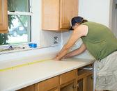 Carpenter Measures Counter Top — Stock Photo