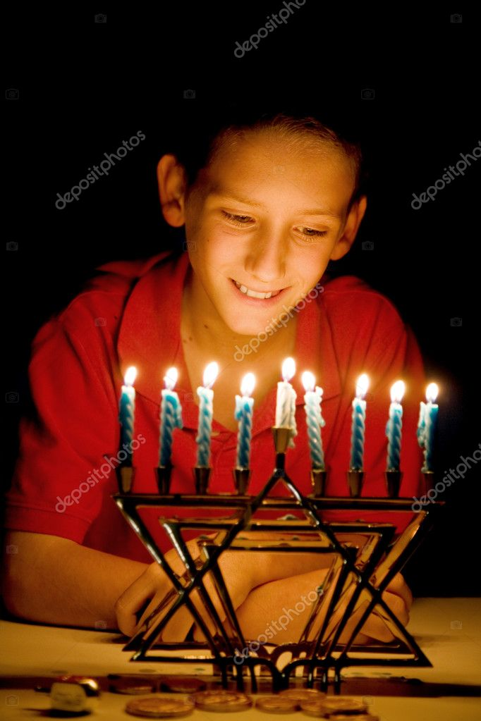 Little boy gazing on a lighted menorah, illuminated only by its light.  Shallow depth of field with focus on boy's eyes. — Stock Photo #6684649