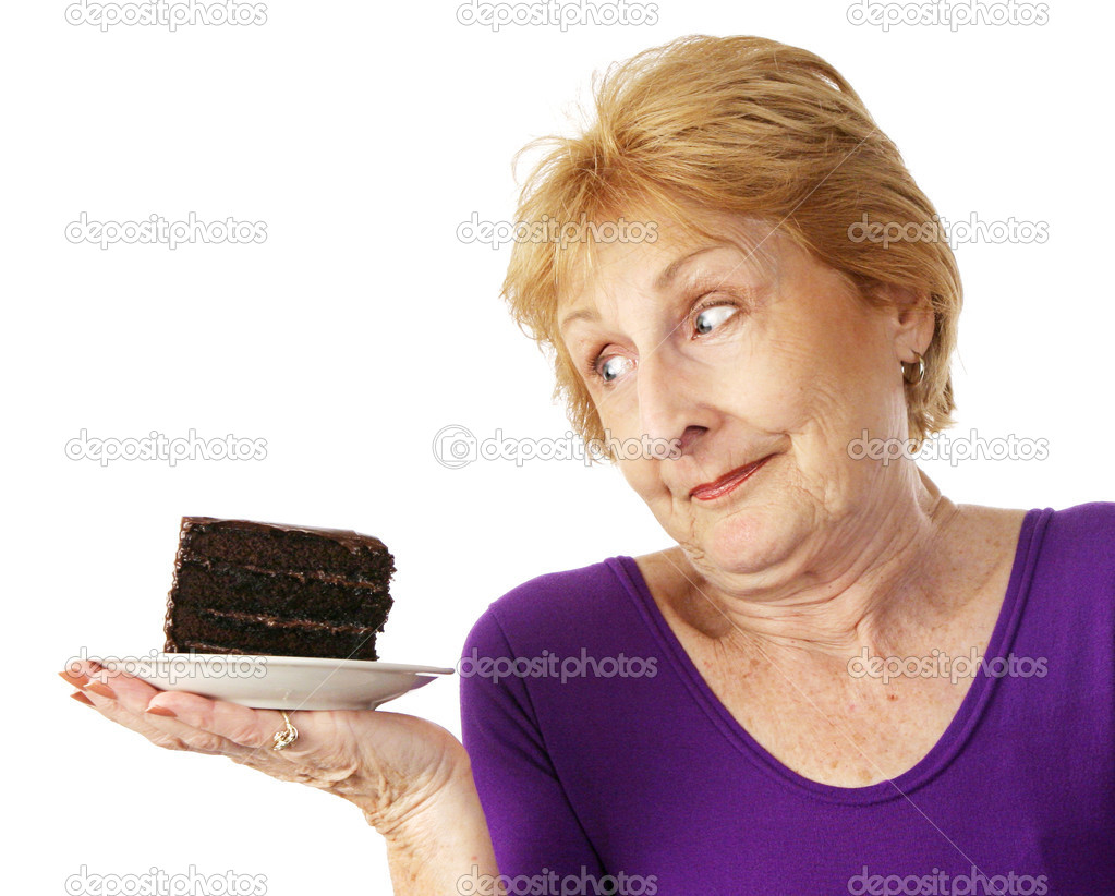 Fit senior woman making food choices.  She is unable to resist the chocolate cake.  Isolated on white.   — Stock Photo #6685133