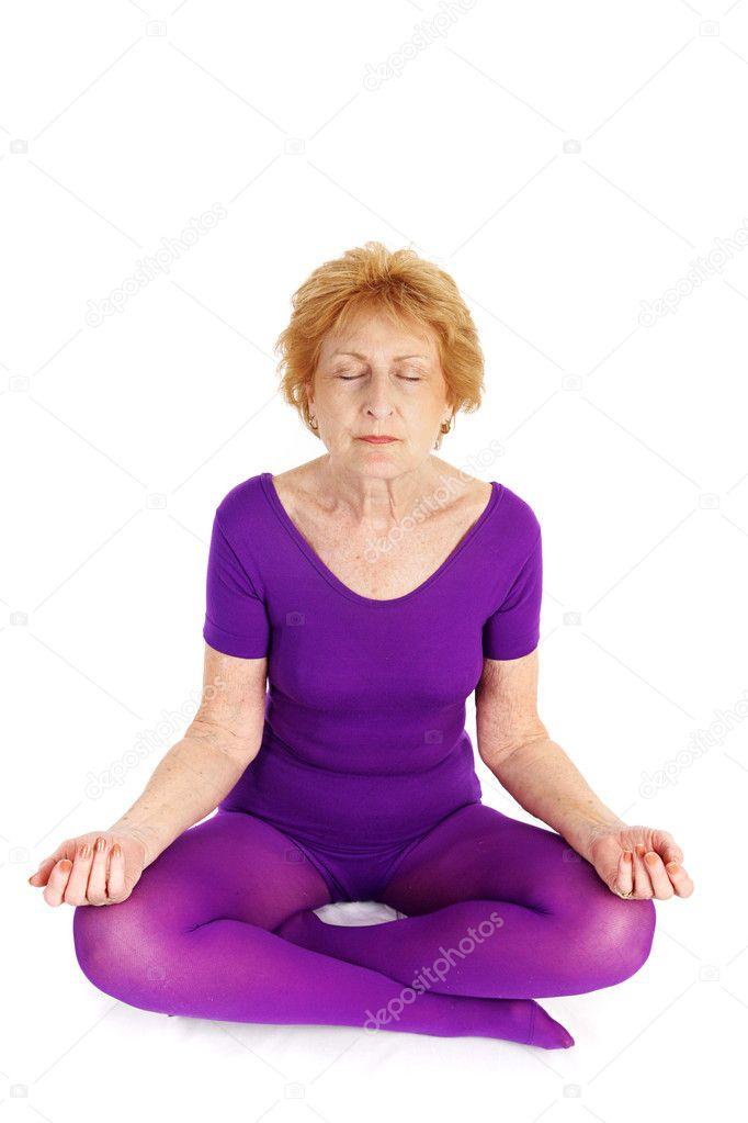 A fit seventy year old woman meditating during a yoga practice.  White background. — Stock Photo #6685183
