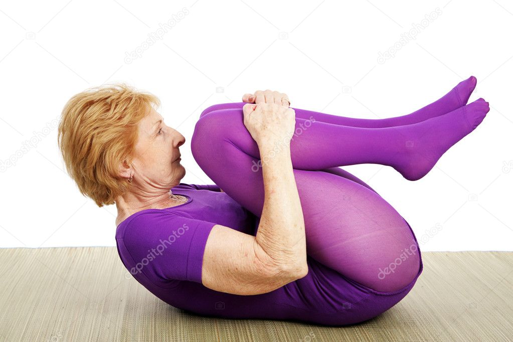 A fit flexible seventy year old woman doing a suppine yoga pose.  White background — Stock Photo #6685192