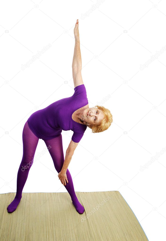 A fit seventy year old woman doing the triangle pose for yoga.  White background.  — Stock Photo #6685194