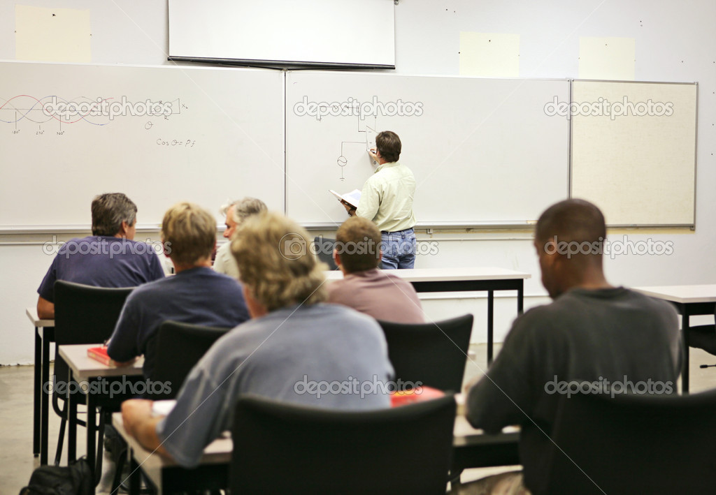An adult education teacher in front of his class, drawing a diagram on the board.  Focus on teacher and diagrams.   — Stock Photo #6685675