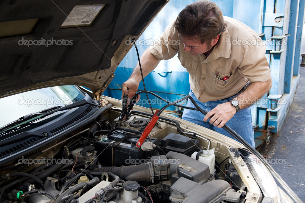 Auto mechanic using jumper cables to charge a car battery. — Stock Photo #6696268