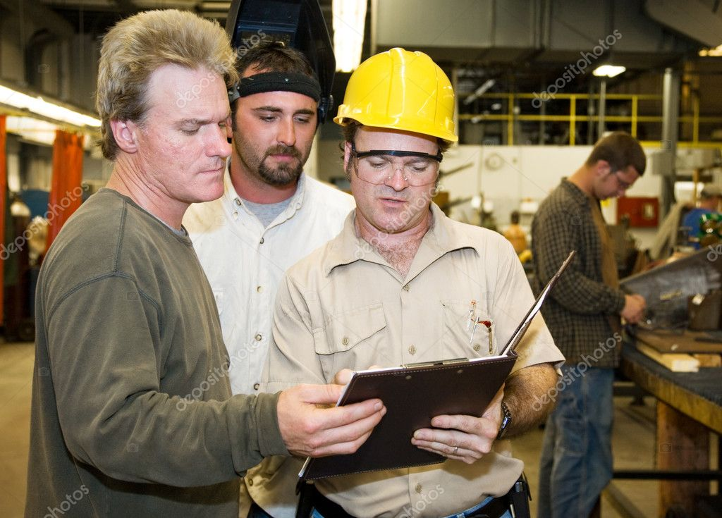 Factory worker and foreman discuss inspection report with auditor.   — Stock Photo #6696277