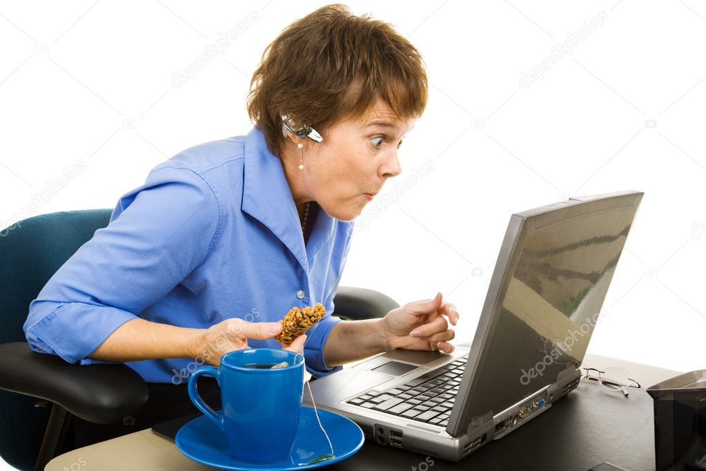 Office worker snacking and browsing the internet, shocked by what she's seeing.  Isolated on white.    Stock Photo #6701018