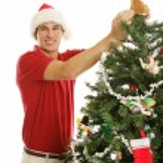 Young Man Decorating Christmas Tree — Stock Photo