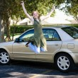 Teen With Car Jumps for Joy - Stock Photo