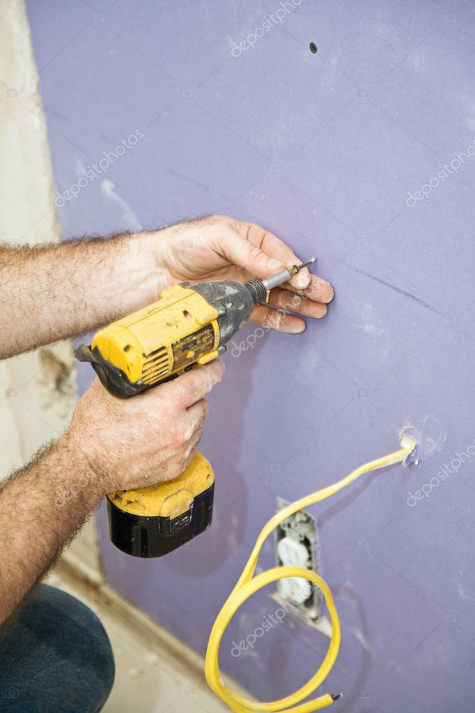 Closeup of contractors hands as he uses a drill to install drywall screws.    Stock Photo #6717465