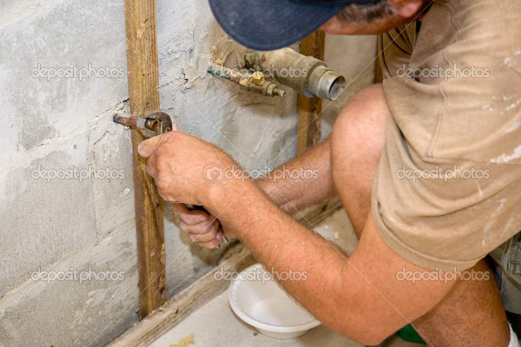 Plumber using channel-lock pliers to attach a nut to a water pipe. He has a bowl beneath to catch any remaining water.   Authentic and accurate content depictio — Stock Photo #6717475