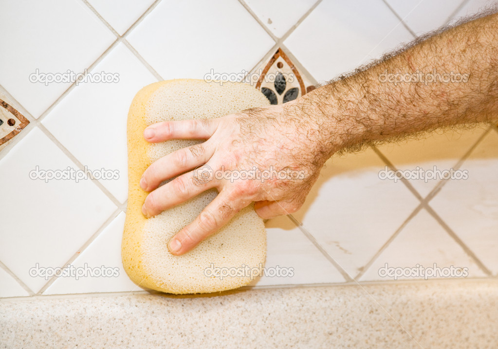 Worker's hand using a sponge to wipe fresh grout from ceramic tile.   — Stock Photo #6717503