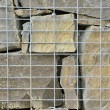 Stone wall texture in the wire reinforcement — Stock Photo