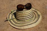 Sonnenhut und sonnenbrille im sand. — Stockfoto