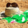 Sun hat, sunglasses and flip-flops on the sand — Stock Photo #6619709