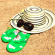Sun hat, sunglasses and flip-flops on the sand — Stock Photo
