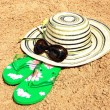 Sun hat, sunglasses and flip-flops on the sand — Stock Photo #6619754