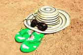 шляпа солнца, солнцезащитные очки и босоножки на песке — Стоковое фото