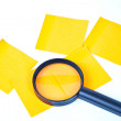A magnifying glass hovering over the post-it Inspection - Stockfoto