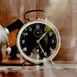 Vintage old alarm clock in glass closet as sepia tone — Stock Photo