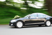 Fast Moving Wedding Car With Bouquet On Hood — Stock Photo