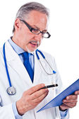 Doctor looking at a case history — Stockfoto