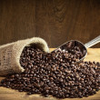 Coffee beans on burlap sack with metal scoop on old plank — Stock Photo #6445017