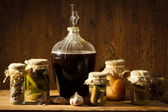 Homemade wine in larder with vegetables jars — Stock Photo