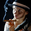 Woman in black hat with smoking cigar and gun black background — Stock Photo #6550336