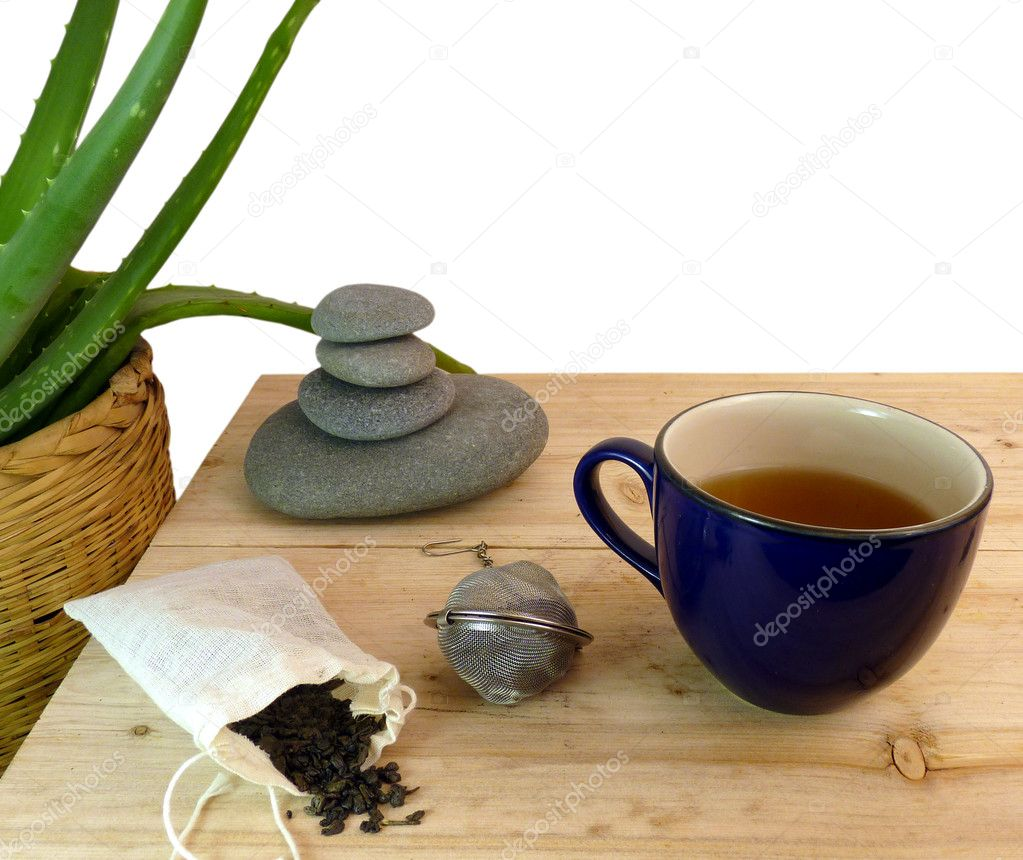 A hot cup of healthy green tea on a rustic pine table with a bulk bag of tea, tea ball, and a stack of zen-like rocks with an aloe plant  Stock Photo #6445585