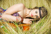 Hippie girl lying on a guitar — Stock Photo