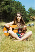 Hippie playing on a guitar — Stock Photo