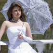 Making look younger bride with umbrella - Stock Photo
