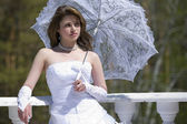Making look younger bride with umbrella — Stock Photo