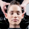 Beautiful young woman getting a hair wash. - Stock Photo