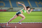 Action packed image of a female sprinter leaving starting blocks — Stock Photo
