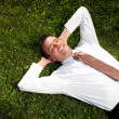 Businessman lying in the grass and relaxing - Stock Photo