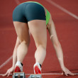 Muscular female sprinter at the starting line in starting blocks ready to b — Foto de Stock
