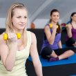Three fit and beautiful young women lifting weights — Stok fotoğraf