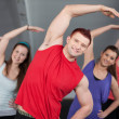Stock Photo: Group of young stretching at health club